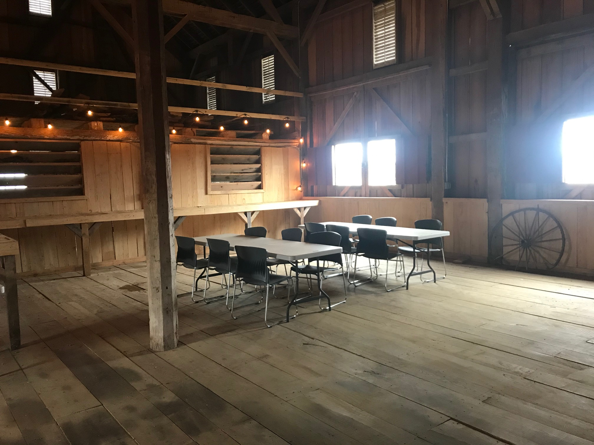 tables and chairs set-up inside creek bend farm barn